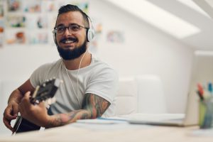 Man with acoustic guitar writing new song in his home recording studio. Using laptop and writing lyrics or music notes. Wearing headphones and playing guitar. Singing and smiling.