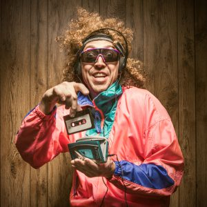 A funky hipster man in late 1980's / early 1990's fashion style, with curly hair and fluorescent colored track suit listening to a walkman tape player and wearing ear muff headphones. He smiles with a cheesy grin, putting a cassette tape into the player with great excitement. Wood paneling in the background. Square crop.