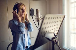 Young smiling woman in with headphones singing in recording studio.